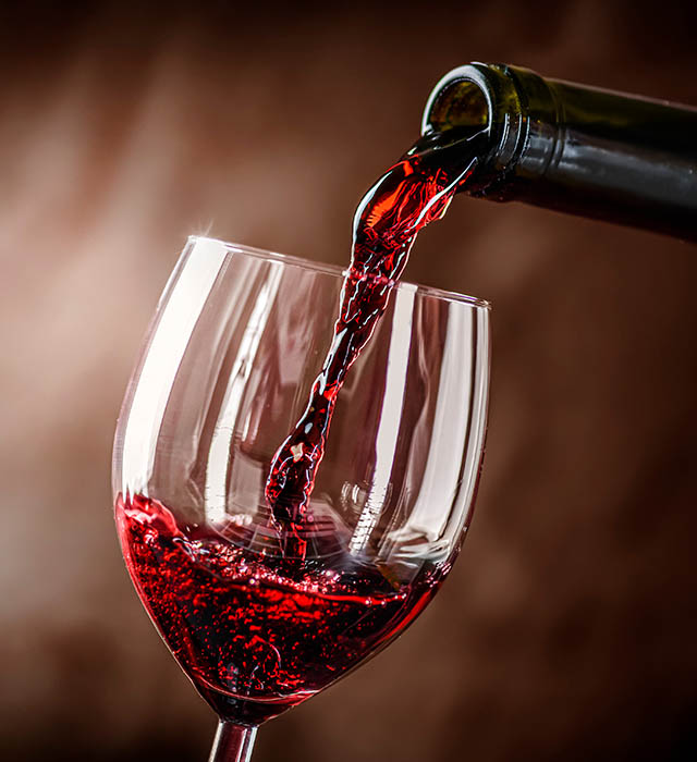 Pouring,Red,Wine,Into,The,Glass,Against,Rustic,Background.,Pour